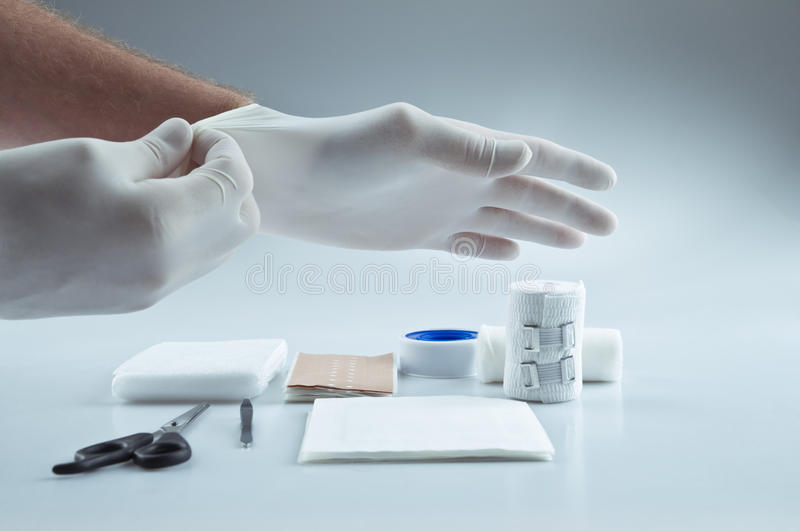 First aid medical supplies. And a doctor putting on protective gloves royalty free stock photography