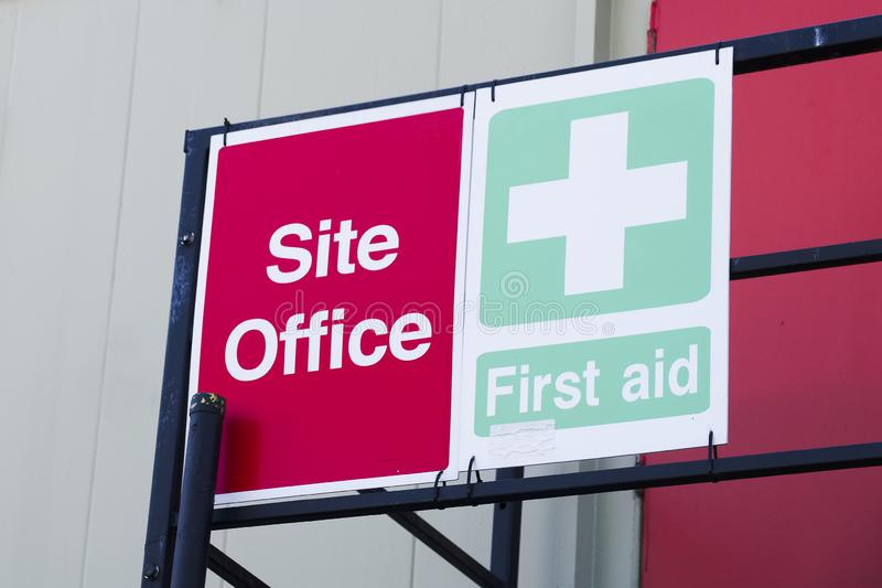 First aid site office sign on construction building door railing for workplace health and safety green cross stock image