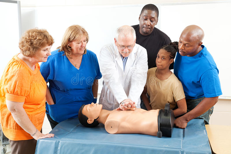 First Aid Training for Adults. Doctor demonstrates CPR for and adult education class on first aid royalty free stock image