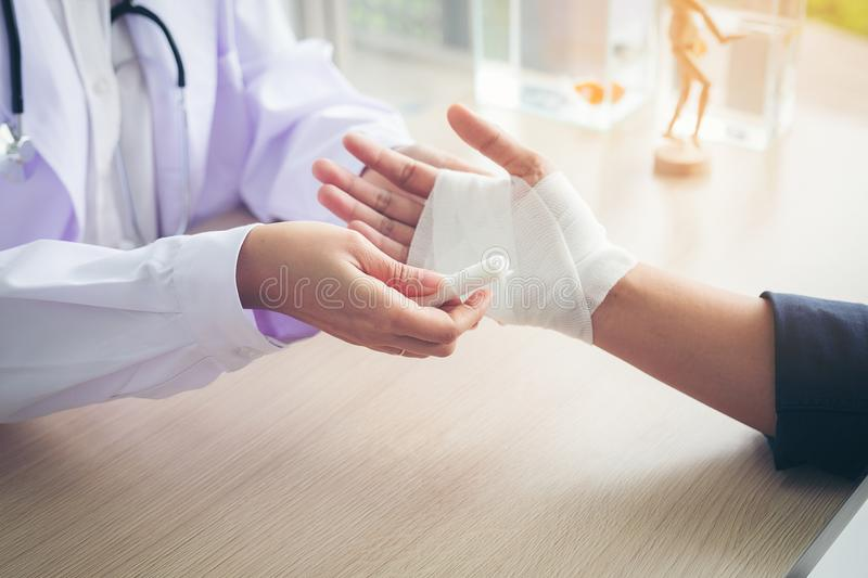 First aid and treatment in wrist injuries and disorders, Traumatologist is taking care of the patient, woman doctor bandaging a h royalty free stock photos