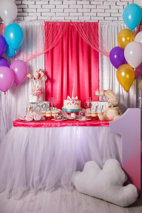 First baby girl birthday party concept. Candy bar with sweet unicorn cakes and decor items in bright pink colors. First baby girl birthday party concept. Candy stock photos