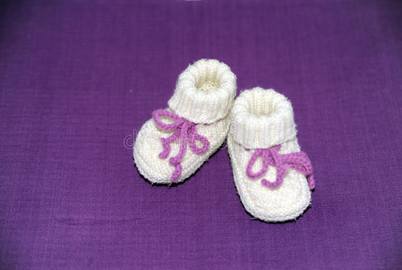 First babyshoes. Lilac babyshoes, knitted from new wool stock photography