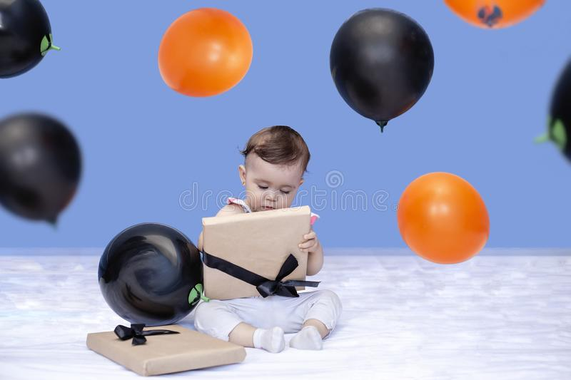 First birthday. Baby girl opening her birthday gift. 1-year-old baby trying to open a birthday present royalty free stock images