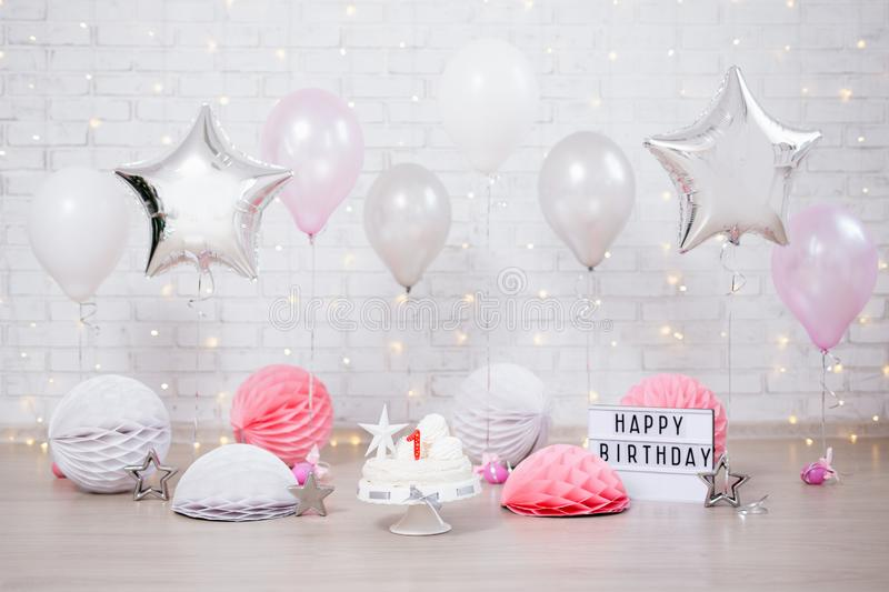 First birthday background - cake, balloons and lightbox with happy birthday text. First birthday background - cake, helium balloons and lightbox with happy stock image