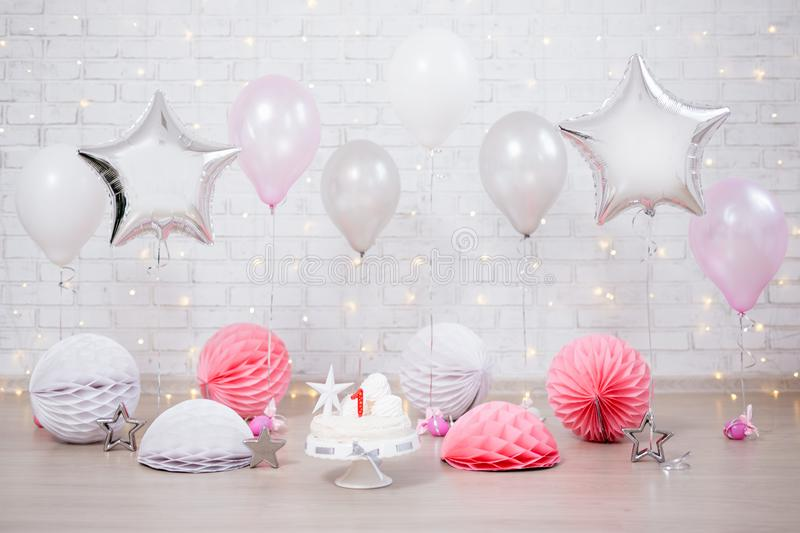 First birthday background - decorated room with cake and balloons over white wall stock photography