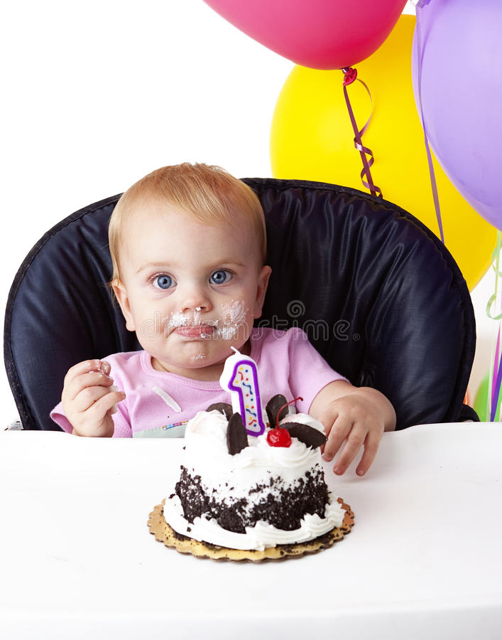 First Birthday Cake. Baby girl sitting in her high chair enjoying her first birthday cake royalty free stock photos