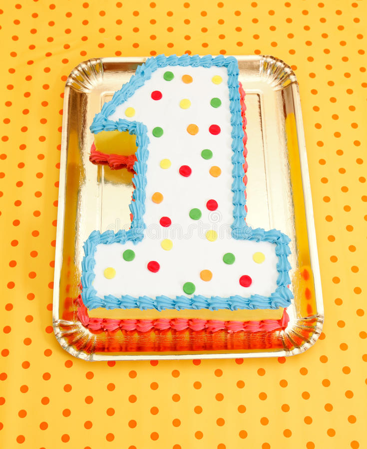 First birthday cake. With colorful candys on dotted background stock photography