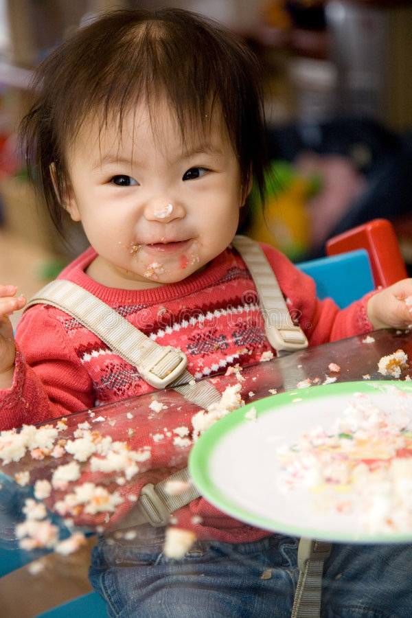 First Birthday Cake. Baby Girl eating her first birthday Cake stock image