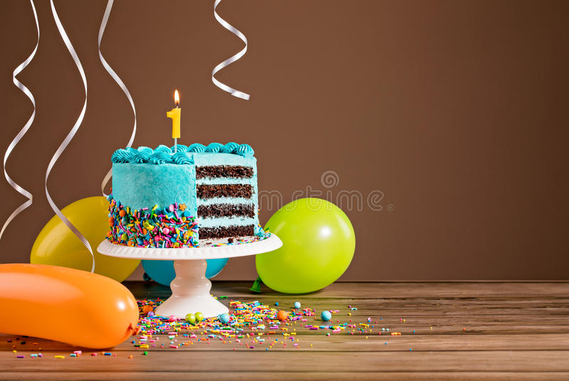 First Birthday Cake. Birthday cake with blue buttercream icing and colorful balloons and a number 1 candle royalty free stock photo