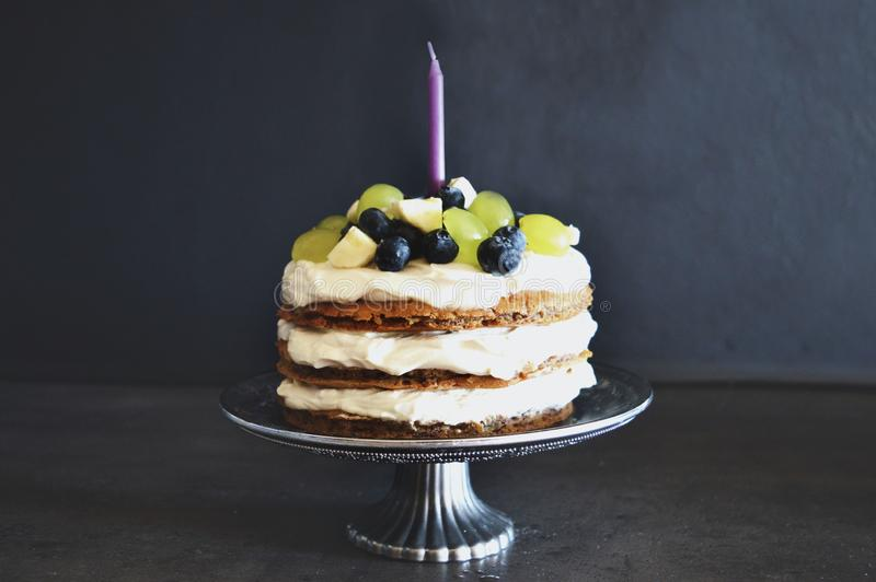 First birthday cake. On silver tray. Cake is made from healthy ingredients with fruits. There`s a purple candle on the cake stock photo