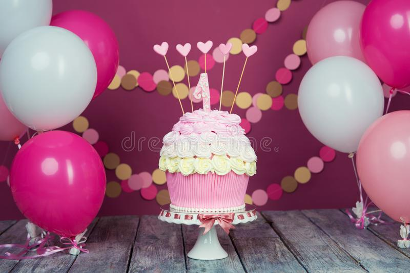 First birthday cake with a unit on a pink background with balls and paper garland. First birthday cake with a unit on a pink background with balls and paper royalty free stock photography