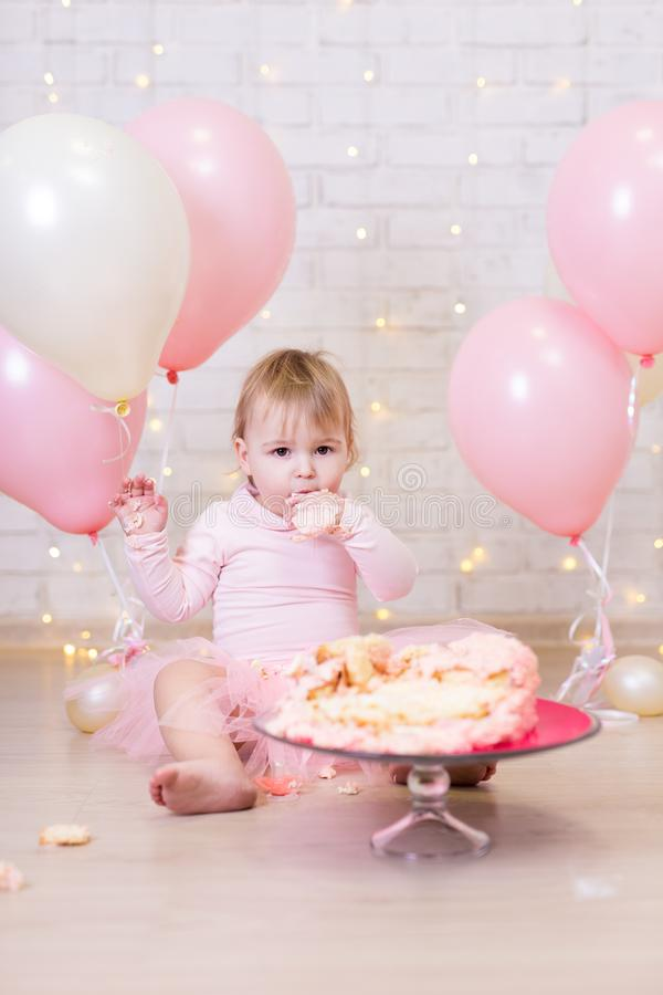 first birthday celebration - funny little girl eating and smashing cake over brick wall background with lights and balloons stock images