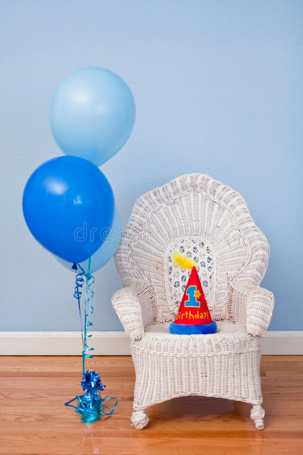 First birthday chair, balloons, hat. A white wicker chair and a 1st birthday hat on the chair. Blue balloons next to the chair. Blue wall, white baseboard, and royalty free stock image