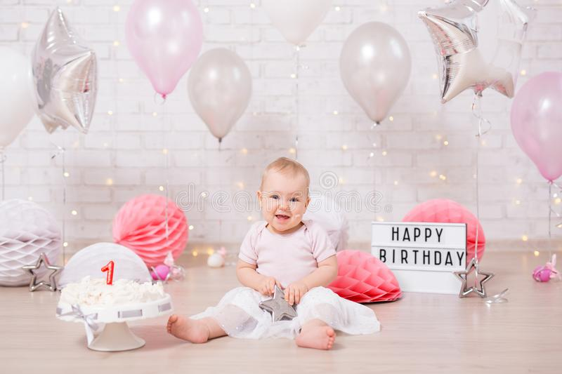 First birthday concept - cute baby girl and smashed birthday cake with lights, stars and balloons stock images