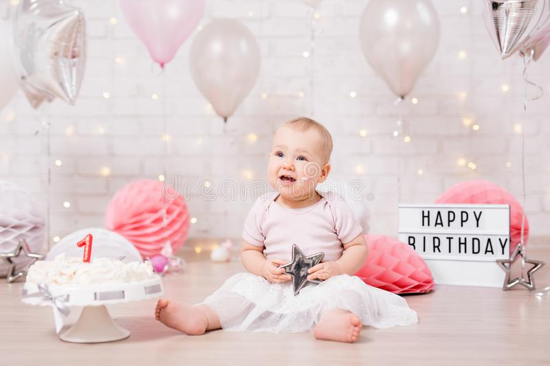First birthday concept - funny dreaming girl and smashed birthday cake with lights, stars and balloons royalty free stock photography