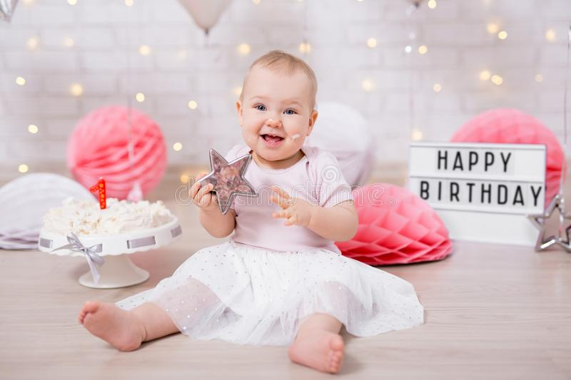 First birthday concept - portrait of cute baby girl holding star and smashed cake with decorations stock photography