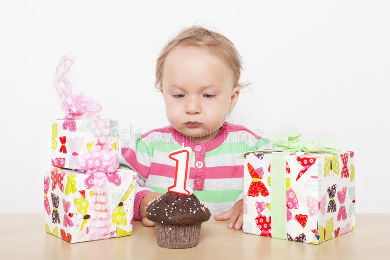 First birthday. Cute baby girl with birthday cake and birthday presents royalty free stock photography