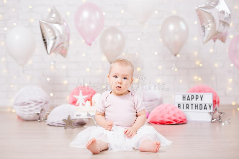 First birthday - cute little baby girl in birtday decorations. With cake and balloons stock image
