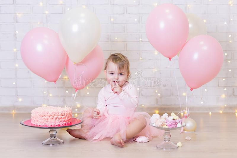 First birthday - cute little girl eating cake over brick wall ba. Ckground with lights and colorful balloons stock photos