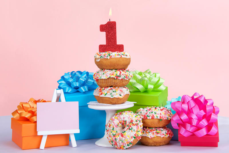 First Birthday Donut Party. Cake donuts with white frosting and colorful sprinkles stacked on and around a small pedestal surrounded by birthday presents. Number royalty free stock image