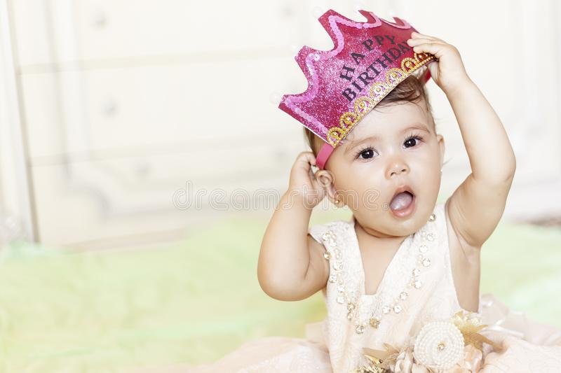 First birthday. Little cheerful baby girl with crown celebrating her first birthday party. A funny baby girl dressed as a princess royalty free stock photos
