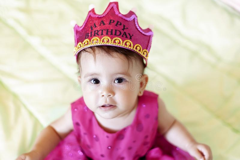 First birthday. Little cheerful baby girl with crown celebrating her first birthday party. A funny baby girl dressed as a princess stock photo