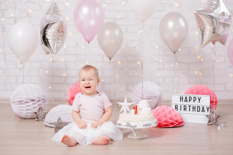 First birthday party concept - cute little girl crying with cake and balloons stock images