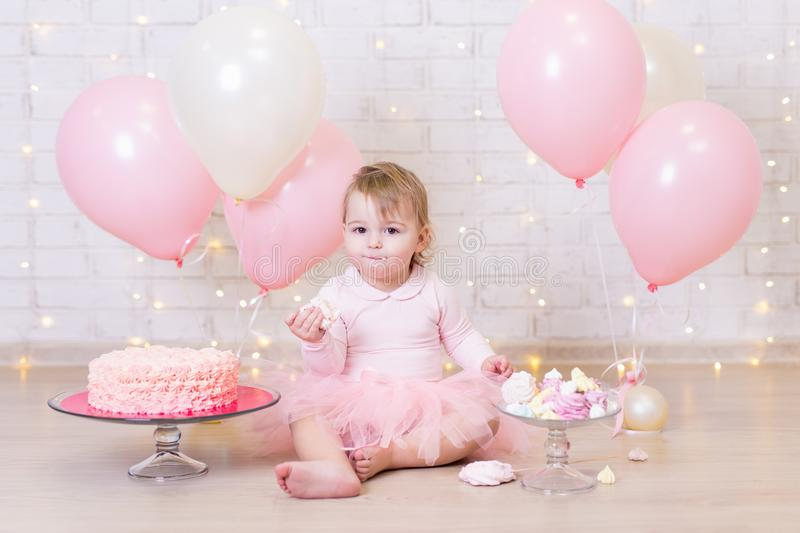 First birthday party concept - cute little girl eating cake over. Brick wall background with lights and colorful balloons stock photo