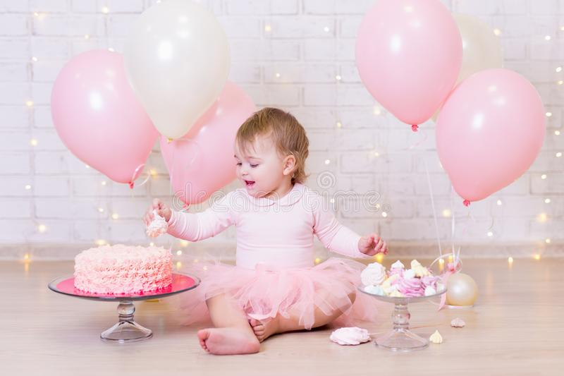 first birthday party concept - funny little girl eating cake over brick wall background with lights and balloons stock photos