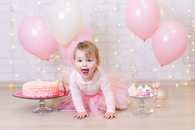 First birthday party and happiness concept - happy little girl w. Ith cake and sweets over brick wall background with lights and colorful balloons royalty free stock image