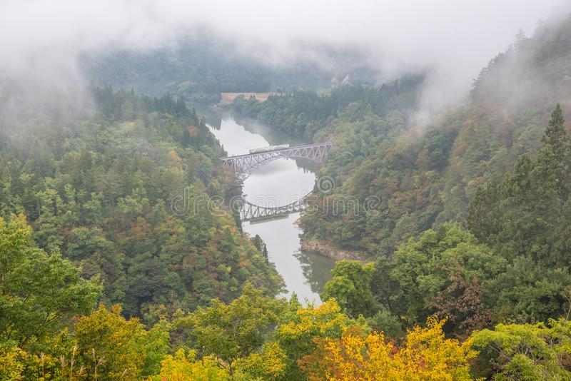Bridge and Tadami river with train crossing the bridge royalty free stock photography