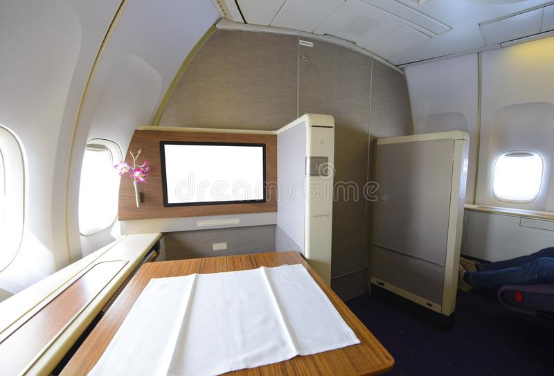 First class cabin with big table and blank screen.  royalty free stock photos