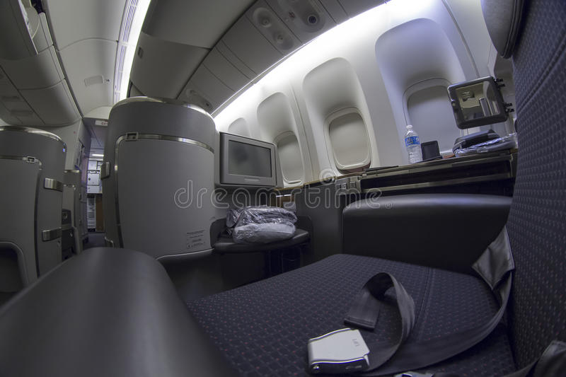 First class seat on Boeing 777-300 in a commercial airplane. A commercial airline's fully flat first class seat and modern entertainment system, duvet bed, and stock images