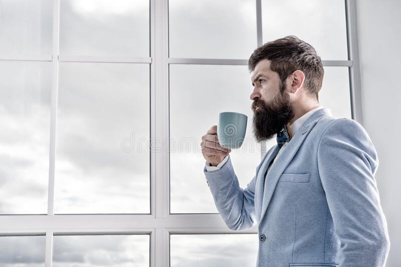 But first coffee. His big day. Wedding morning concept. Wedding day. Groom bearded hipster man wear blue tuxedo and bow stock image