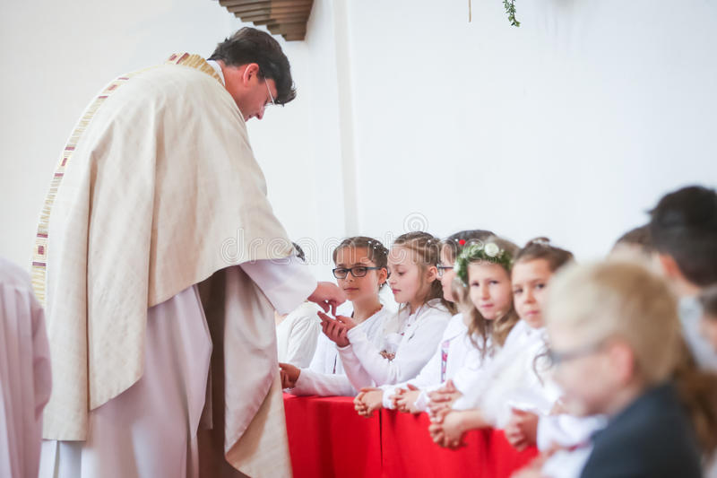 First communion. NANDLSTADT, GERMANY - MAY 7, 2017 : The priest giving young boys and girls the sacramental bread at their first communion in Nandlstadt, Germany royalty free stock photos