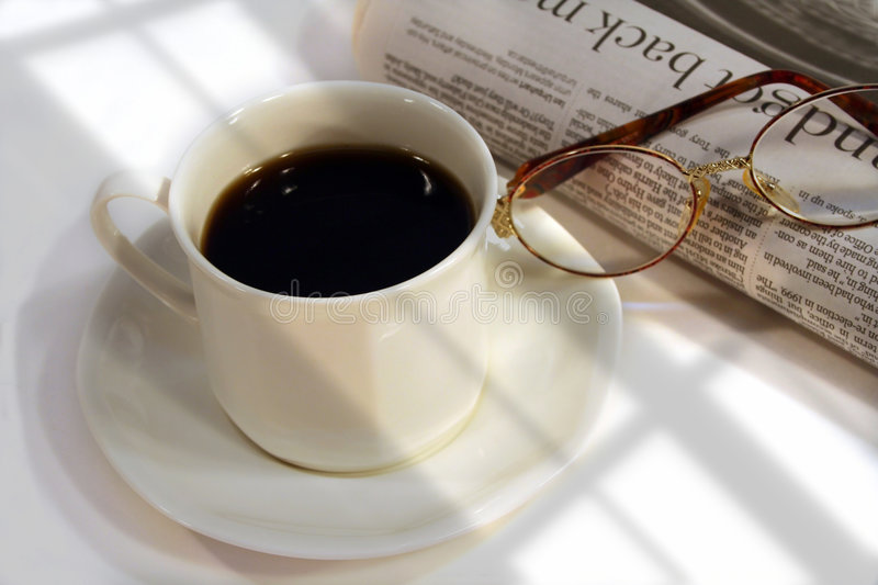 First cup of the day. Filtering light from a window on a cup of coffee and morning newspaper stock photo