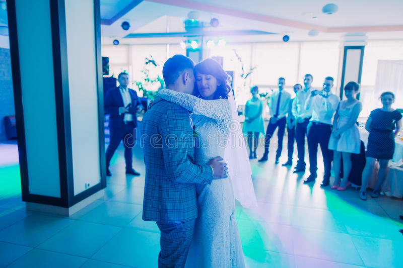 The first dance of the newlyweds in the blue lighting. stock photography