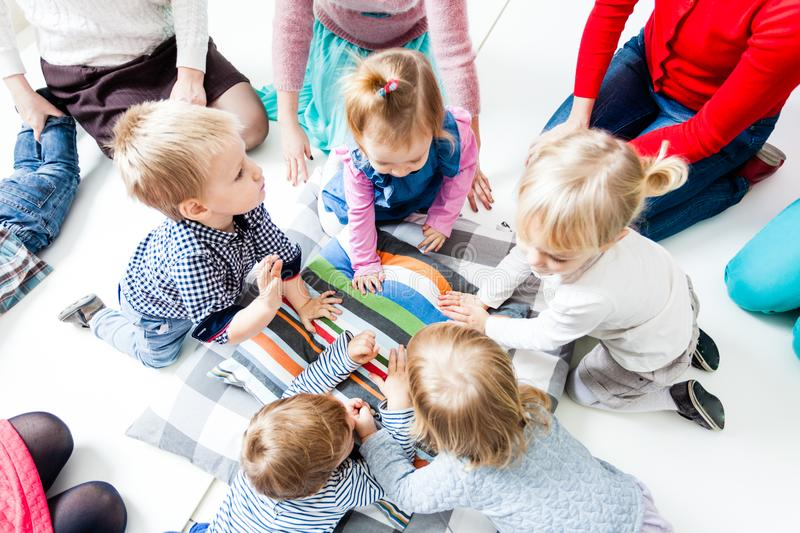 First day of children in the kindergarten. The first acquaintance of children in the kindergarten. Moms acquaint children to each other. Moms playing with their stock photos