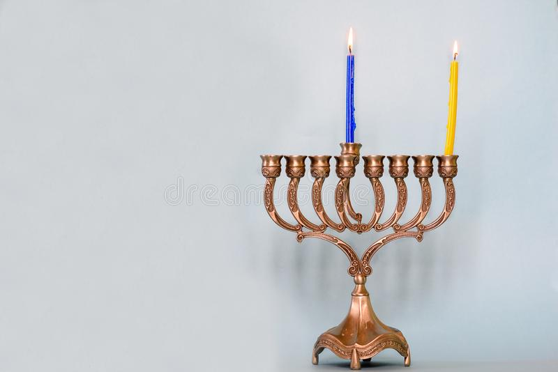 First day of Hanukkah with burning Hanukkah colorful candles in Menorah traditional Candelabra. Chanukkah-jewish holiday. Each night, another candle is added stock photo