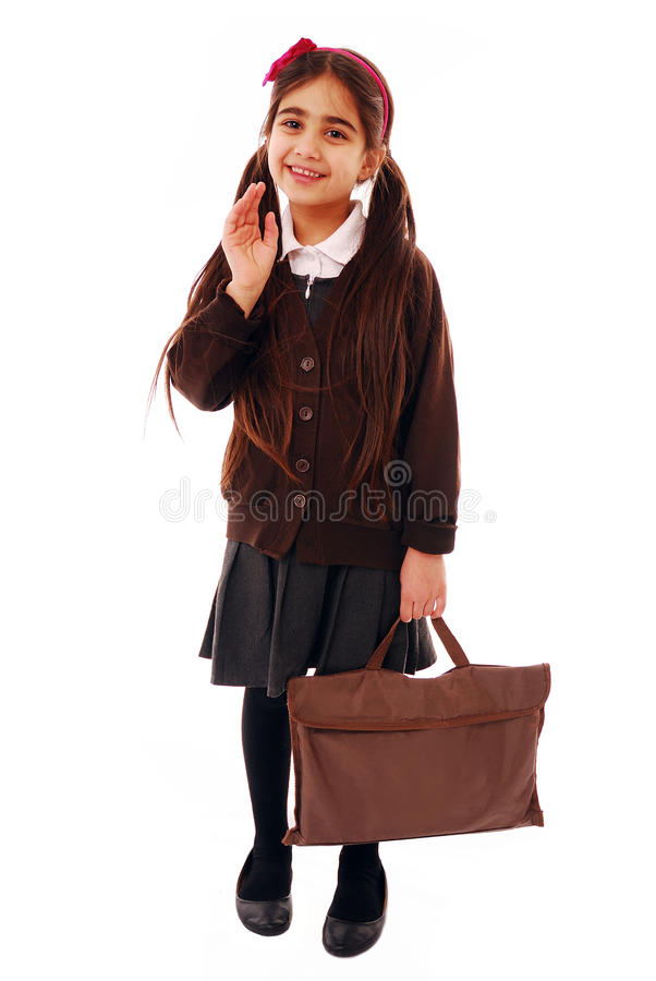 First day at school. Schoolgirl waving goodbye isolated on white stock photo