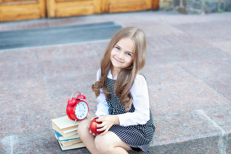 First day of school. Back to school. Child girl schoolgirl elementary school student sits on the steps near the school and holds a stock image