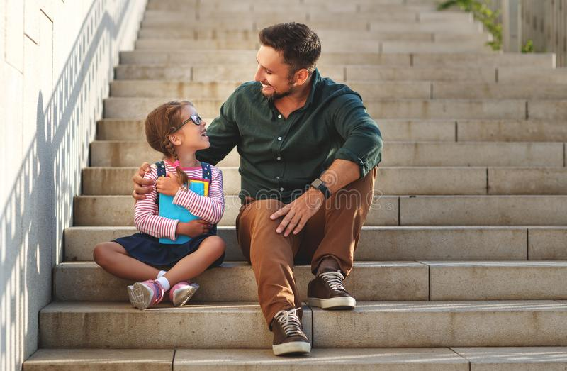 First day at school. father leads little child school girl in f royalty free stock photos