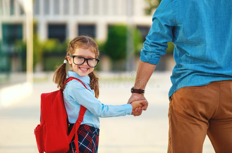 First day at school. father leads  little child school girl in first grade. First day at school. father leads a little child school girl in first grade royalty free stock photography