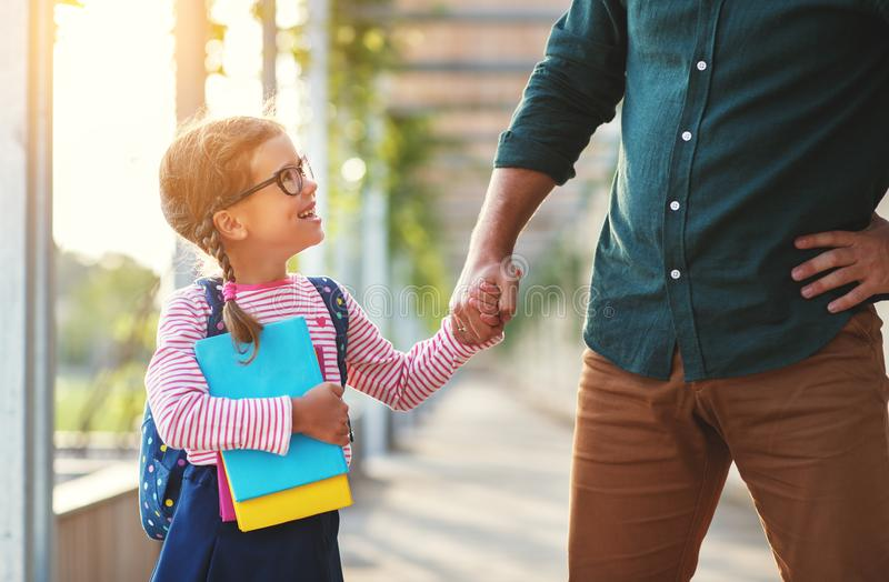 First day at school. father leads little child school girl in f. First day at school. father leads a little child school girl in first grade royalty free stock images