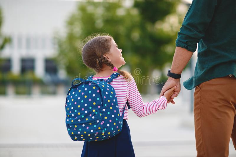 First day at school. father leads little child school girl in f stock photography