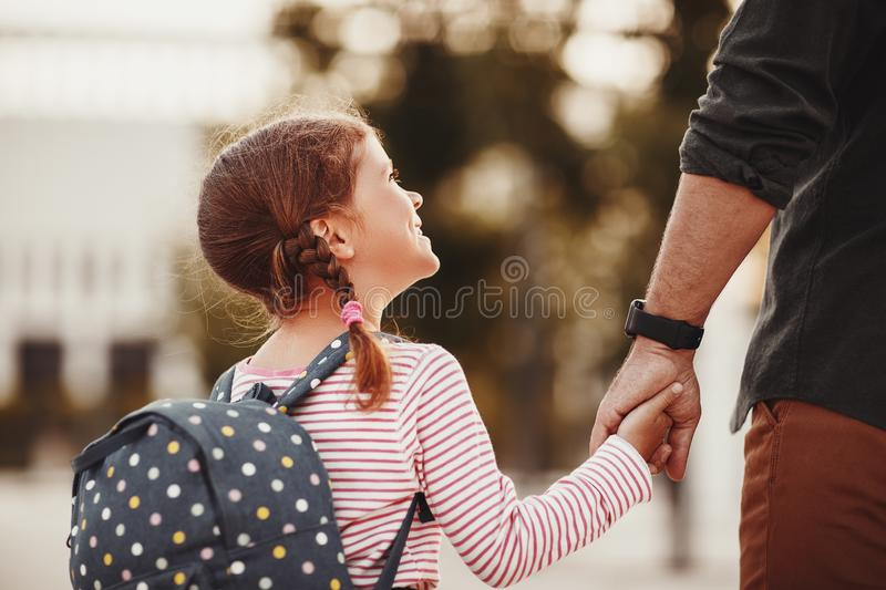 First day at school. father leads  little child school girl in first grade royalty free stock image