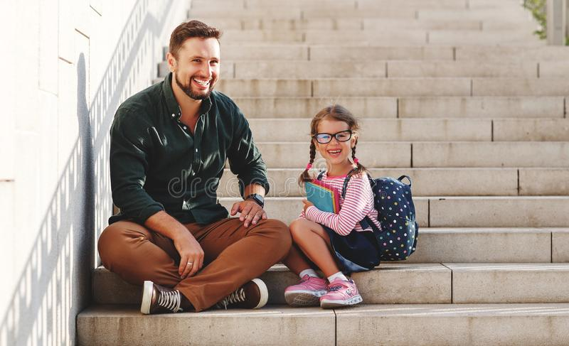 First day at school. father leads  little child school girl in first grade. First day at school. father leads a little child school girl in first grade royalty free stock photo