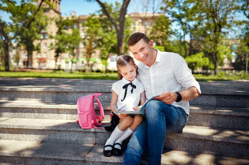 First day at school. Father and little kid daughter sitting on stairs and read book, study lessons. Parenthood and child stock images