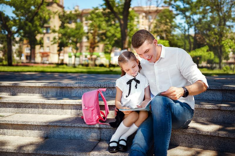 First day at school. Father and little kid daughter sitting on stairs and read book, study lessons. Parenthood and child royalty free stock images