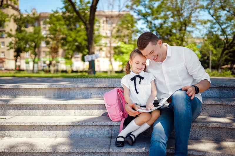 First day at school. Father and little kid daughter sitting on stairs and read book, study lessons. Parenthood and child royalty free stock photo